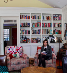 Castleton University president Dr. Karen Scolforo is seen sitting in a comfortable chair in front of a bookcase in her new home.