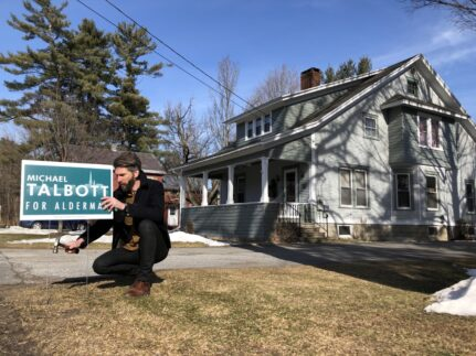 "Michael Talbott crouched in front of a home, planting a ""Talbott for alderman"" campaign sign."